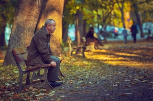 BUCHAREST, ROMANIA - OCTOBER 23, 2013: Unidentified lonely thoughtful retired man on his 60s rests on a bench in a park, autumn scene. The retirees represents 22% of the Bucharest's total population.