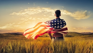 Young man wrapped American flag crop field sunset
