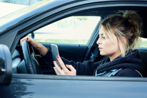 Woman driving car distracted by her mobile phone