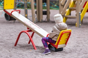 Little cute caucasian girl in jacket and hat sitting alone on a seesaw swing at a playground outdoors. Loneliness mood concept